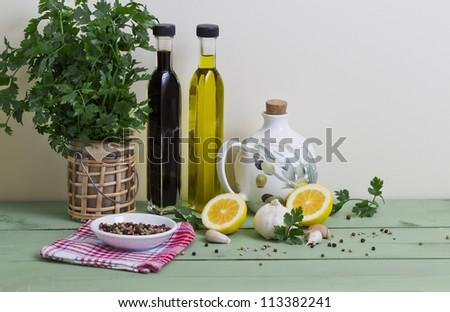 Fresh parsley, garlic, balsamic vinegar, olive oil, peppercorns and lemon on a table.