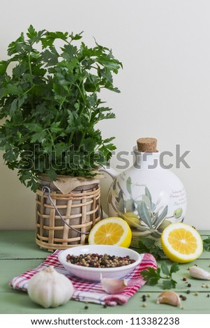 Fresh parsley, garlic, olive oil, peppercorns and lemon on a table.