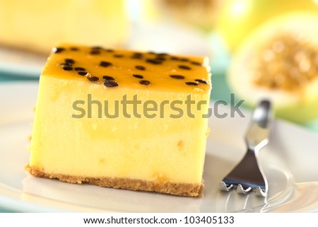 Fresh passion fruit cheesecake dessert on plate with pastry fork (Selective Focus, Focus on the upper edge of the cake)