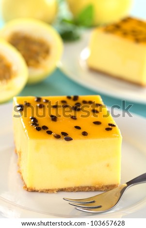 Fresh passion fruit cheesecake dessert on plate with pastry fork with another cake and yellow passion fruits in the back (Selective Focus, Focus on the left upper front edge of the cake)
