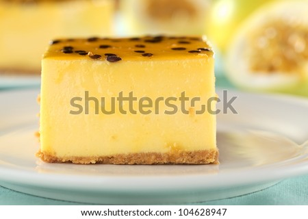 Fresh passion fruit cheesecake dessert on plate with yellow passion fruits in the back (Selective Focus, Focus on the front of the cake)