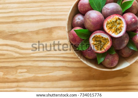 Fresh passion fruit in wood bowl on wood table in top view flat lay with copy space for background or wallpaper. Ripe passion fruit so sweet and sour. Tropical fruit.