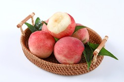 Fresh Peach fruits with leaves in a basket on a white.Bite of a peach fruit.
