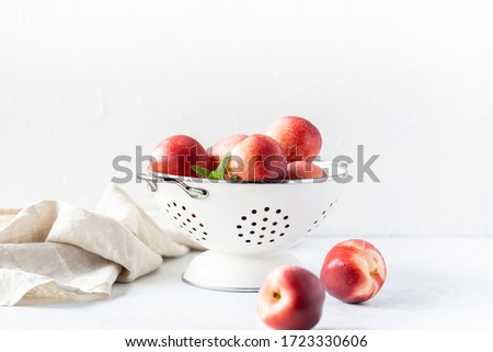 Fresh peaches and nectarines for a delicious Breakfast in a white iron bowl on a white background. The concept of delicious and healthy food. Copy space.