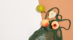 Fresh peaches and pears in a mesh bag or string bag.  Zero waste. Eco life vegan concept.  Flat lay. Minimal