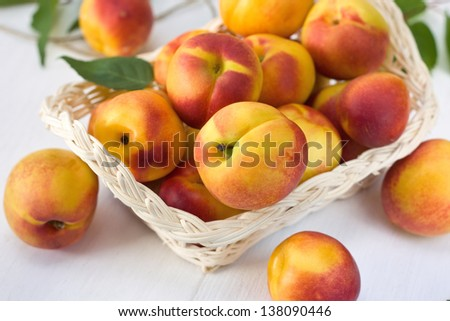 Fresh Peaches (Nectarine) in a basket on a wooden board - stock photo