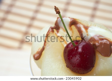 Fresh pear and cherry desert with melted white and milk chocolate topping