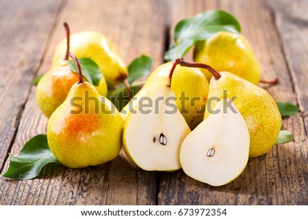 fresh pears with leaves on wooden table