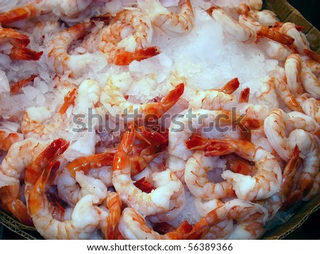 Fresh peeled prawns on ice at a seafood market.