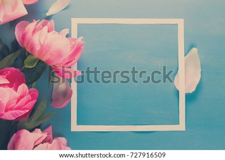 Fresh peony flowers with paper frame close up, copy space on blue background, retro toned #727916509