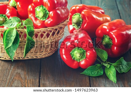 fresh pepper on the table. red sweet pepper close-up. paprika in a wicker basket. background with bell peppers.