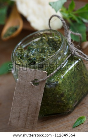 Fresh pesto sauce in a jar with blank card