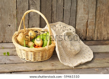 Fresh picked organic vegetables and a straw hat on a grunge wood background.