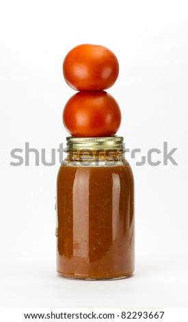 Fresh picked tomatoes stacked on a mason jar of homemade tomato sauce