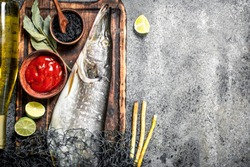 Fresh pike with sauce, spices, herbs and white wine. On a rustic background.