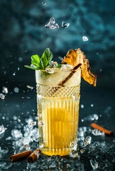 Fresh pineapple cocktail with cinnamon and ice in jar glass on dark blue background. Studio shot of drink in freeze motion, flying ice, drops in liquid splash. Summer cold drink and cocktail