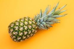 Fresh pineapple on yellow background