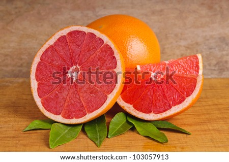 fresh pink grapefruit and leaves on a wooden background