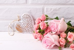 Fresh pink roses flowers  and decorative heart  on  white wooden background. Floral still life.  Selective focus. Place for text.
