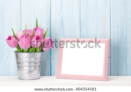 Fresh pink tulip flowers bouquet and blank photo frame with copy space on shelf in front of wooden wall