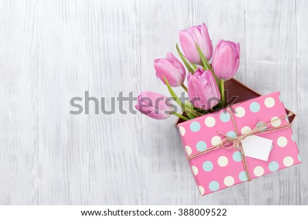 Fresh pink tulip flowers in gift box on wooden table. Top view with copy space