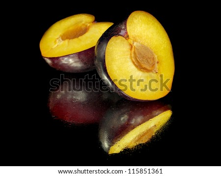 fresh plum on a black background with water drops