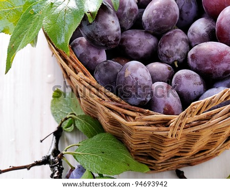 Fresh plums in basket on white background