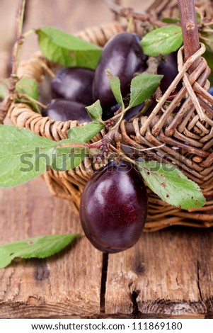 Fresh plums in basket on wooden table