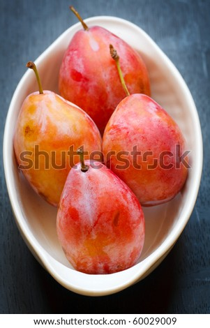 Fresh plums in the white bowl,shallow focus