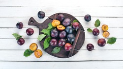 Fresh plums with leaves. Fruits. On a white wooden background. Top view. Free space for your text.