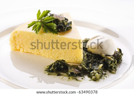 Fresh polenta with spinach and cream close up