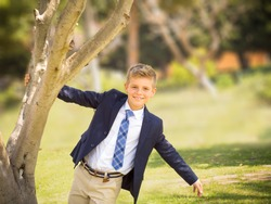 fresh portrait of a boy dressed in a suit and tie in a park for a special event like a communion or wedding