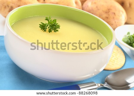 Fresh potato cream soup garnished with a parsley leaf with green onion and raw potatoes in the back on a blue table mat (Selective Focus, Focus on the parsley leaf in the bowl)