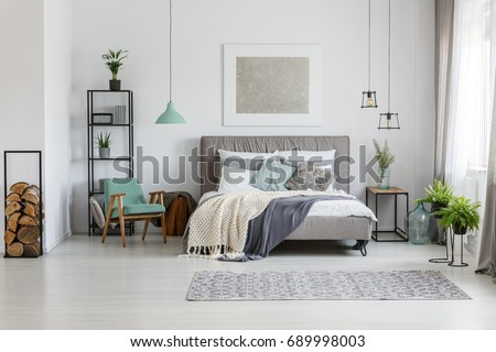Fresh potted plants in bright room with poster above the bed #689998003