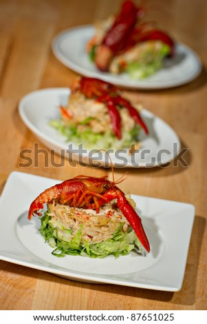 Fresh prepared Crayfish beautifully plated over a round of green lettuce topped with a seafood salad.