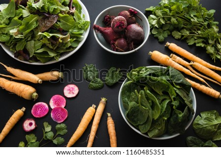 Fresh produce from the local farm including mixed greens, spinach, carrots, and beets on black background.