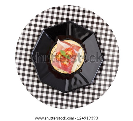 Fresh Prosciutto and Provolone cheese with baby tomato on a poppy and sesame seed cracker; garnished with a sprig of fresh basil.  Isolated with clipping path.