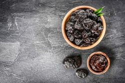 Fresh prunes in wooden bowl. Prunes on stone dark table. Prunes healthy food. Dried plums and jam in bowl.