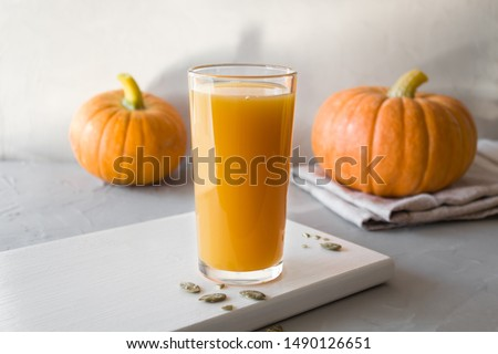 Fresh pumpkin juice in a glass Cup with seeds and orange pumpkins. Healthy and tasty food concept. Autumn harvest. Copy space, minimalism, horizontal orientation, selective focus. #1490126651
