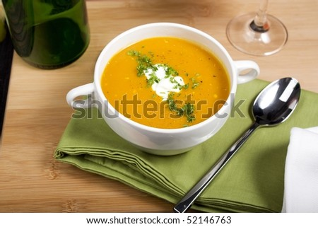 Fresh pumpkin soup on green napkin.