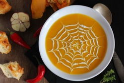 Fresh pumpkin soup with a picture of a spider web, cobweb  of cheese cream served on a board with garlic, pumpkin, chilli pepper and crouton on Halloween  .
