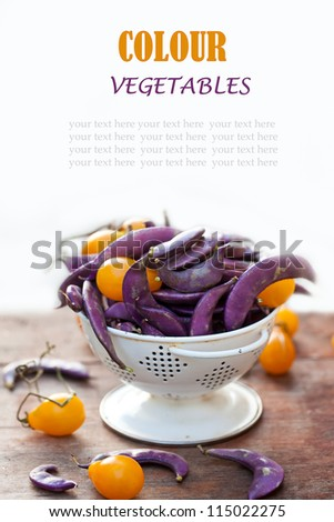 Fresh purple beans and yellow tomatoes in the white colander with space for text.