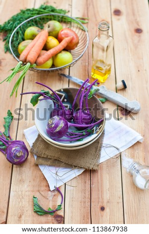 fresh purple kohlrabi in bowl  with root vegetables in the background on a wooden table
