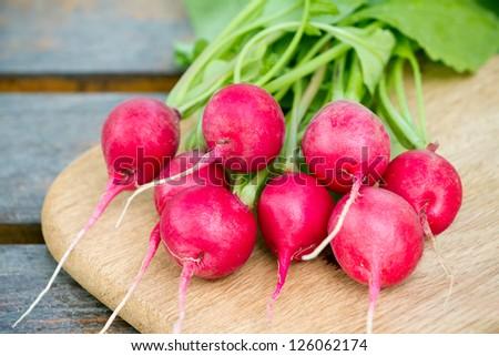 Fresh radishes on a wooden cutting board