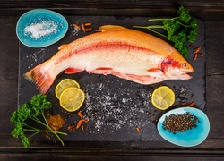 fresh rainbow trout fish with spices on dark wooden table, preparation