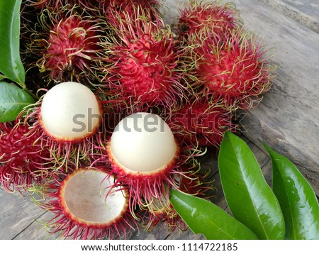 fresh rambutan isolate with green leaf. Fresh Rambutan in bamboo basket on wooden table background