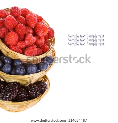 Fresh raspberries, blackberries and blueberries in a wicker baskets isolated on white background