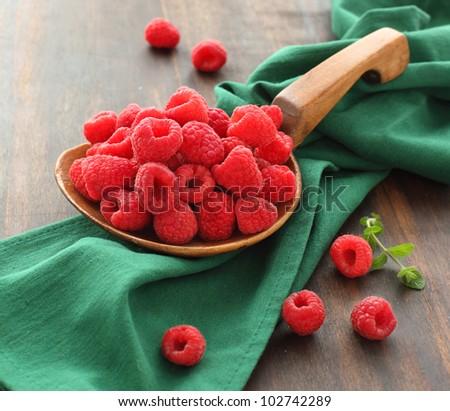Fresh raspberries in a big wooden spoon