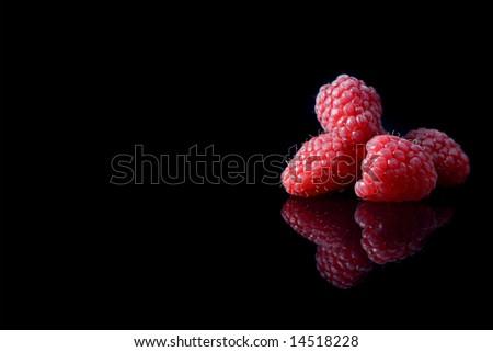 Fresh raspberries isolated on black background