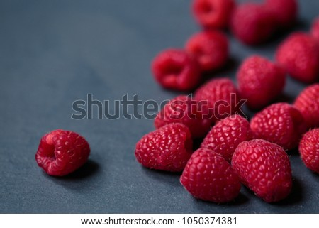Fresh raspberries on dark stone background. Close up. Selective focus. #1050374381